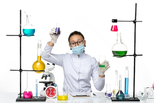 Front view female chemist in medical suit with mask holding different solutions on a white background splash virus chemistry lab covid-