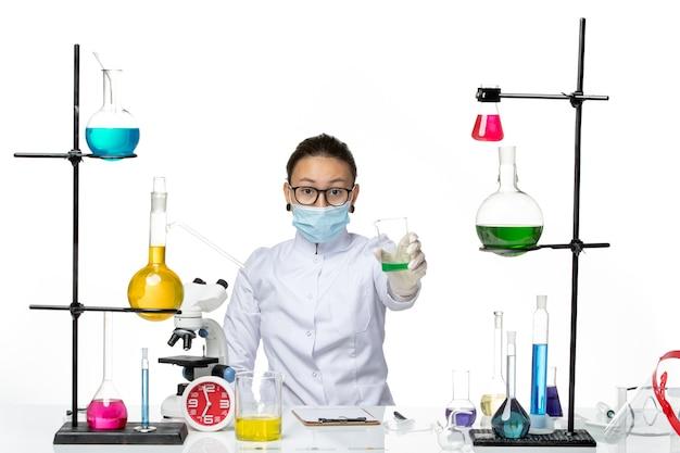 Vista frontale farmacista femmina in tuta medica con maschera tenendo la soluzione verde su sfondo bianco chiaro splash laboratorio virus chimica covid-
