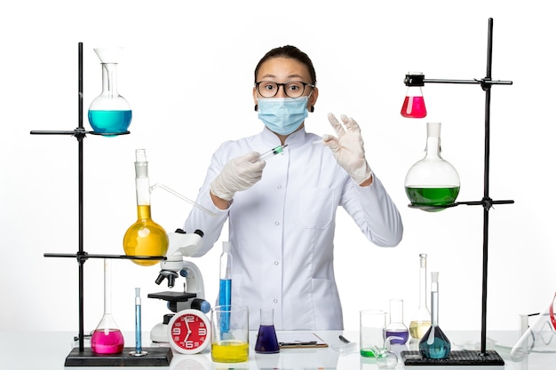 Front view female chemist in medical suit with mask holding injection on white background virus chemistry lab covid splash