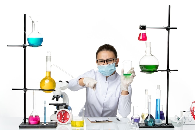 Front view female chemist in medical suit with mask holding solution on a light-white background splash lab virus chemistry covid-