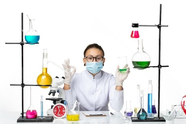 Vista frontale femmina chimico in tuta medica con maschera che tiene la soluzione sulla luce sfondo bianco splash laboratorio virus chimica covid-