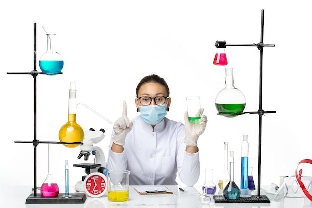 Chimico femminile di vista frontale in vestito medico con la soluzione della tenuta della maschera su fondo bianco covid chimica del virus del laboratorio della spruzzata