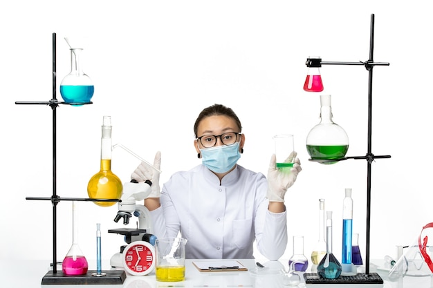 Farmacia femminile di vista frontale in vestito medico con la soluzione della tenuta della maschera sulla chimica del virus del laboratorio della spruzzata della scrivania bianca