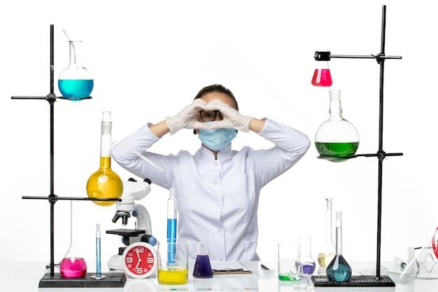 Chimico femminile di vista frontale in vestito medico con la maschera che si siede davanti al tavolo con soluzioni sullo splash covid del laboratorio di chimica del virus del fondo bianco chiaro