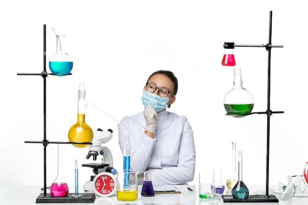 Chimico femminile di vista frontale in vestito medico con la maschera che si siede davanti al tavolo con soluzioni che pensano su spruzzata covid del laboratorio di chimica del virus del fondo bianco