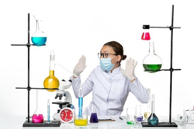 Chimico femminile di vista frontale in vestito medico con la maschera che si siede davanti al tavolo con soluzioni su spruzzata covid del laboratorio di chimica del virus del fondo bianco
