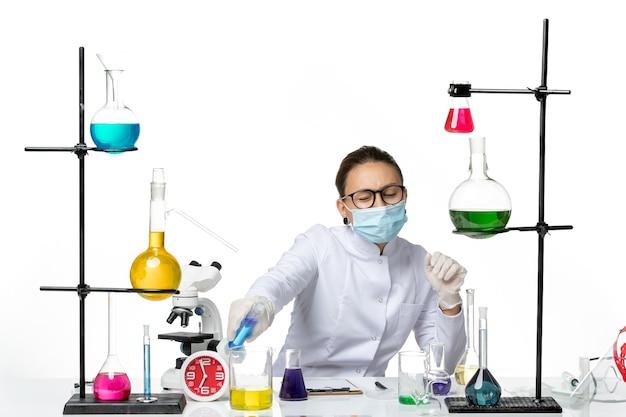 Chimico femminile di vista frontale in vestito medico con la maschera che si siede all'interno della stanza con le soluzioni sul tavolo su spruzzata covid del laboratorio di chimica del virus del fondo bianco