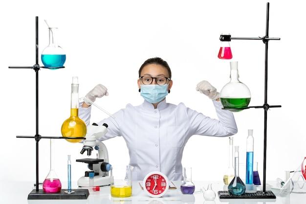Chimico femminile di vista frontale in vestito medico con la maschera che si siede con le soluzioni e che flette sulla spruzzata covid di chimica del laboratorio del virus del fondo bianco