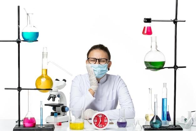 Chimico femminile di vista frontale in vestito medico con maschera che si siede con soluzioni che hanno mal di denti su sfondo bianco laboratorio virus chimica covid- splash