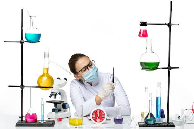 Front view female chemist in medical suit with mask sitting with solutions holding pen on white background splash lab virus chemistry covid