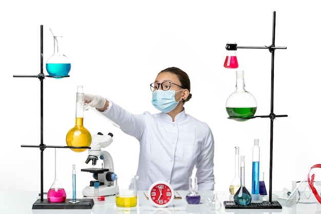 Front view female chemist in medical suit with mask sitting with solutions on light-white background chemistry lab virus covid- splash