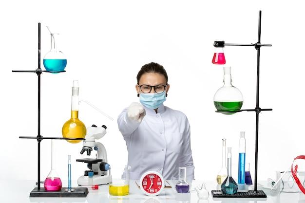 Chimico femminile vista frontale in tuta medica con maschera seduto con soluzioni su sfondo bianco chiaro chimica laboratorio virus covid-splash