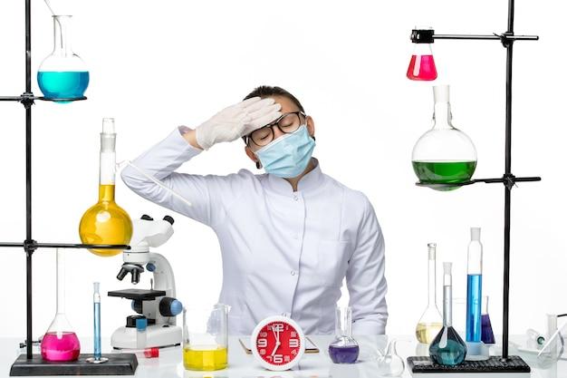 Chimico femminile vista frontale in tuta medica con maschera seduto con soluzioni sullo sfondo bianco chiaro chimica virus laboratorio covid-splash