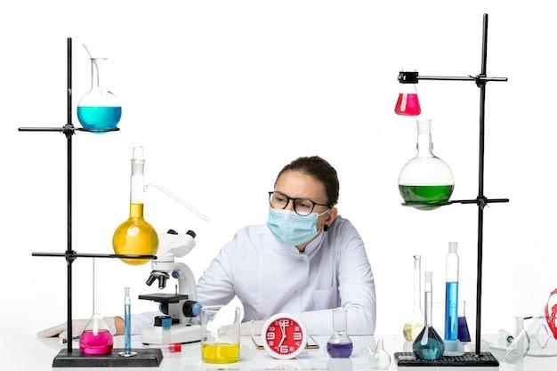 Chimico femminile di vista frontale in vestito medico con la maschera che si siede con le soluzioni sul laboratorio covid di chimica del virus della spruzzata del fondo bianco chiaro