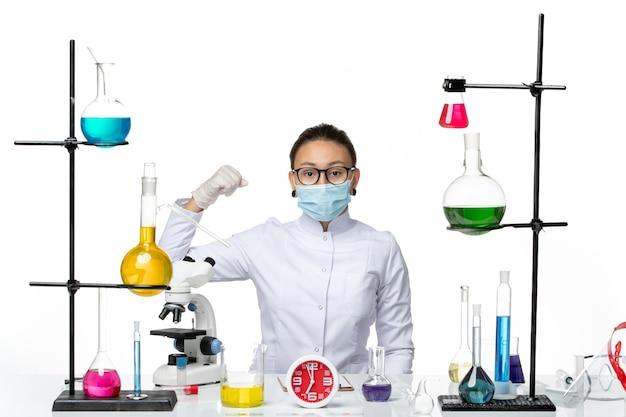 Chimico femminile di vista frontale in vestito medico con la maschera che si siede con le soluzioni su una spruzzata covid di chimica del laboratorio del virus del fondo bianco chiaro