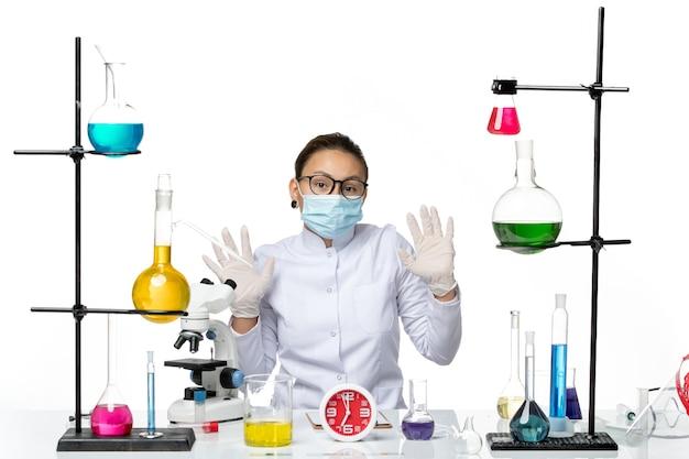 Chimico femminile di vista frontale in vestito medico con la maschera che si siede con le soluzioni sul laboratorio covid di chimica del virus della spruzzata del fondo bianco