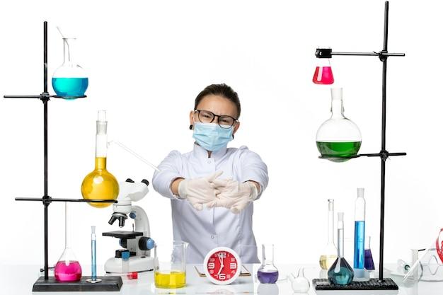 Chimico femminile di vista frontale in vestito medico con la maschera che si siede con le soluzioni su un laboratorio covid di chimica del virus della spruzzata dello scrittorio bianco