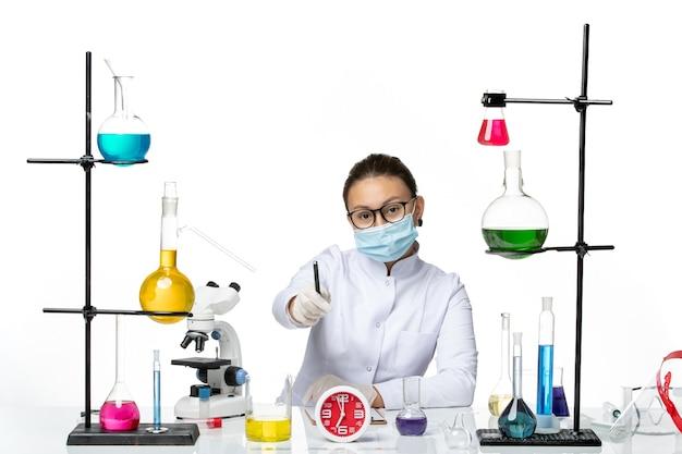 Vista frontale farmacista femmina in tuta medica con maschera seduta con soluzioni scrivere note su sfondo bianco chiaro laboratorio chimico covid virus- splash