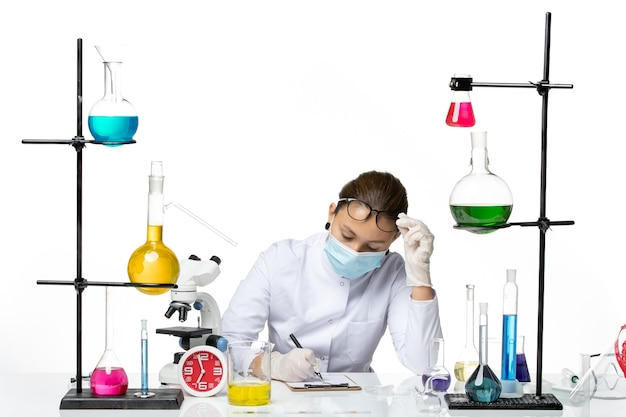 Front view female chemist in medical suit with mask sitting with solutions writing notes on white background splash lab virus chemistry covid