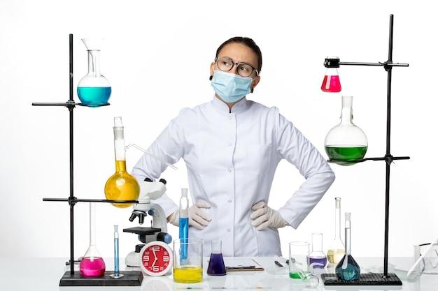 Chimico femminile vista frontale in tuta medica con maschera pensando su sfondo bianco laboratorio di chimica del virus covid-splash