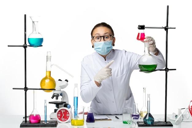Chimico femminile di vista frontale in vestito medico con la maschera che lavora con le soluzioni sulla spruzzata covid del laboratorio di chimica del virus della scrivania bianca