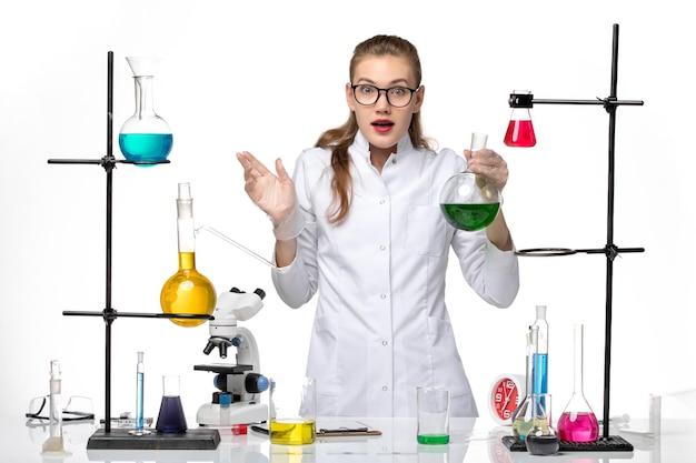 Chimico femminile vista frontale in tuta medica nel processo di lavoro con soluzioni su sfondo bianco chiaro virus pandemia covid chimica