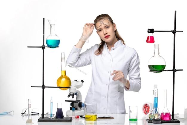 Chimico femminile vista frontale in tuta medica nel processo di lavoro con soluzioni su sfondo bianco virus covid pandemia chimica