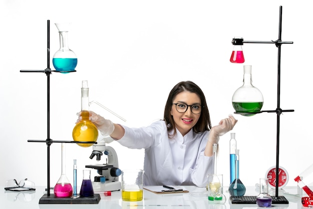 Front view female chemist in medical suit working with solutions on white background lab virus covid- pandemic science