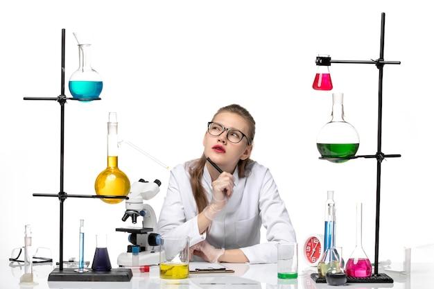 Chimico femminile vista frontale in tuta medica scrivere note e pensare su sfondo bianco chimica pandemia salute covid