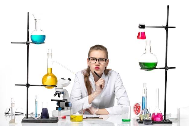 Chimico femminile vista frontale in tuta medica scrivere note su sfondo bianco chimica pandemia salute covid
