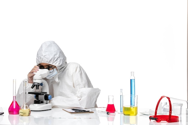 Front view female chemist in special protective suit checking sample using microscope on white background chemistry covid- pandemic health virus