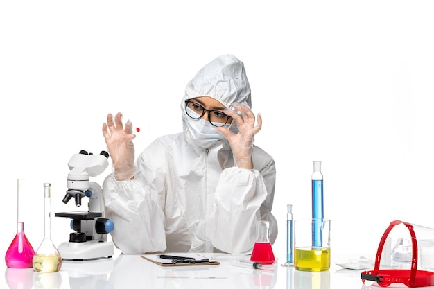 Front view female chemist in special protective suit checking sample on white background virus chemistry covid pandemic