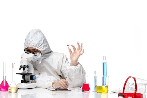 Front view female chemist in special protective suit checking sample on white desk virus chemistry covid pandemic health