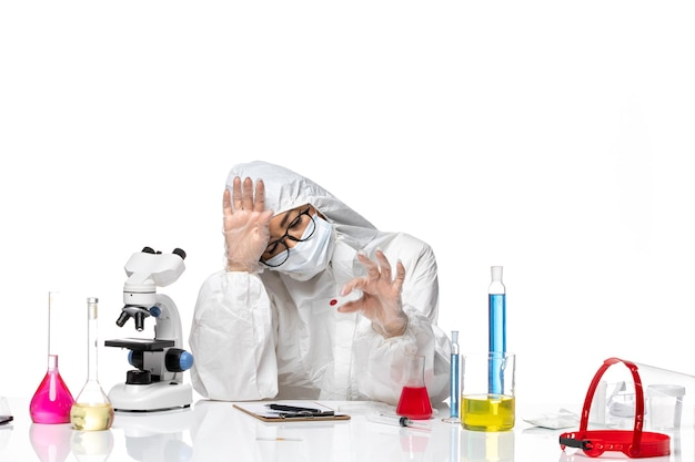 Front view female chemist in special protective suit checking sample on white floor virus chemistry covid- pandemic health