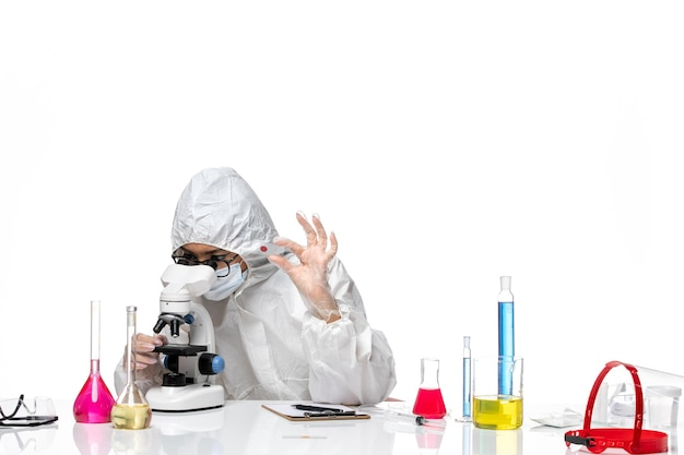Front view female chemist in special protective suit checking samples on white background virus chemistry covid- pandemic health
