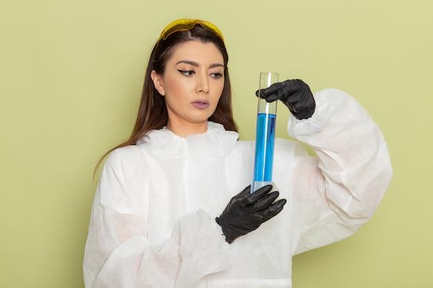 Chimico femminile di vista frontale nella boccetta della tenuta della tuta protettiva speciale con la soluzione blu sulla superficie verde