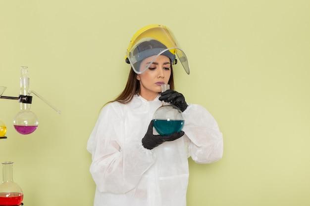 Chimico femminile di vista frontale in vestito protettivo speciale che tiene boccetta con soluzione blu e odore sulla superficie verde