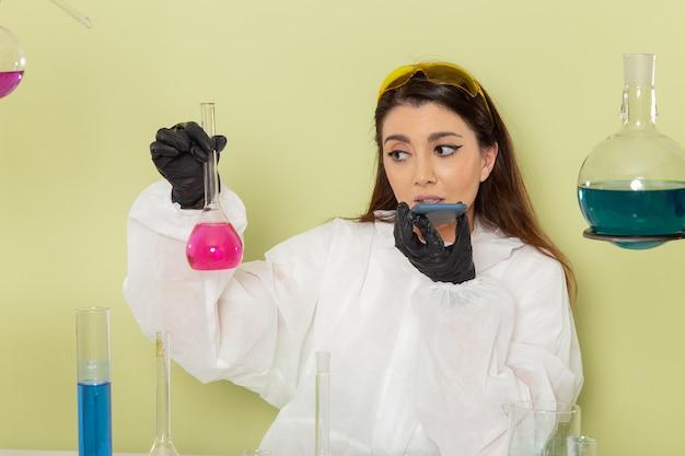 Chimico femminile di vista frontale nella boccetta della tenuta della tuta protettiva speciale con la soluzione rosa sulla superficie verde