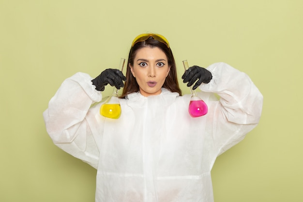 Front view female chemist in special protective suit holding flasks with solutions on light green surface