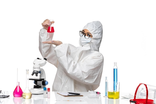Front view female chemist in special protective suit holding red solution on the white background covid- chemistry virus lab