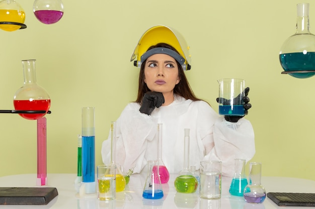 Front view female chemist in special protective suit working with solutions on the green surface