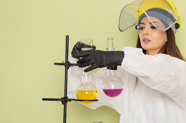 Front view female chemist in special protective suit working with solutions on light-green surface