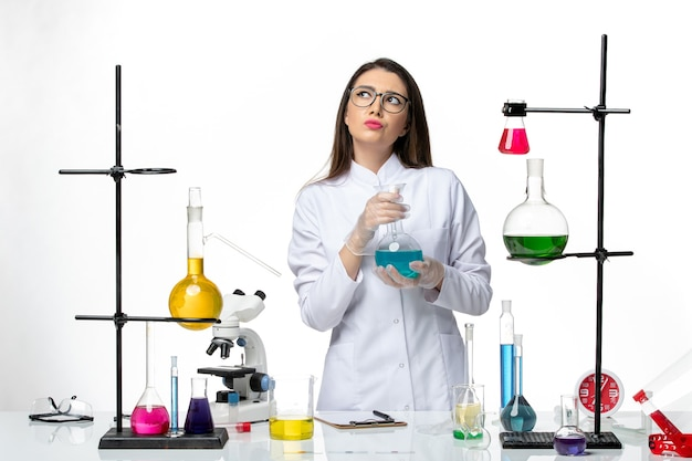 Front view female chemist in sterile medical suit holding flask with solution on a white background virus covid- pandemic science