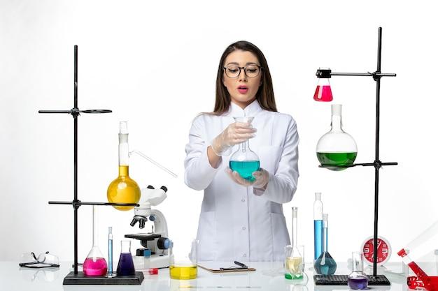 Chimico femminile di vista frontale in fiaschetta sterile della tenuta del vestito medico con la soluzione su fondo bianco scienza covid-pandemica del virus