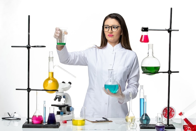 Front view female chemist in sterile medical suit holding flasks with solutions on light white background virus covid- pandemic science