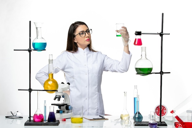Front view female chemist in sterile medical suit working with solutions on light white background lab virus covid- pandemic science