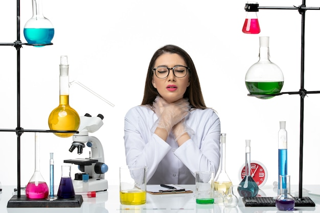 Chimico femminile di vista frontale in vestito medico bianco che si strozza su fondo bianco laboratorio covid del virus pandemico di scienza