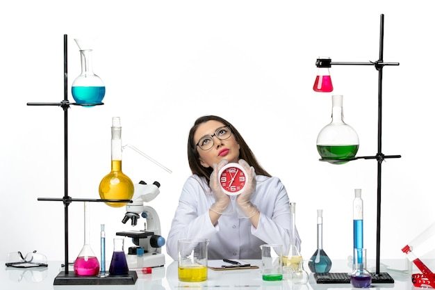 Front view female chemist in white medical suit holding clocks on a white background science virus lab covid- pandemic