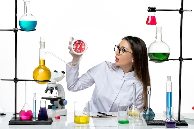 Front view female chemist in white medical suit holding clocks on white background science virus lab covid pandemic