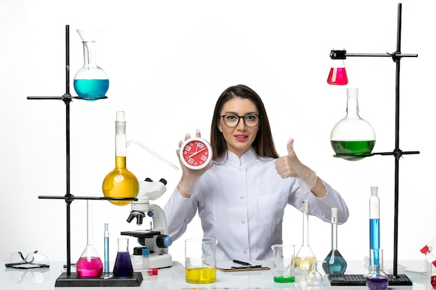 Front view female chemist in white medical suit holding clocks on white desk science virus lab covid pandemic